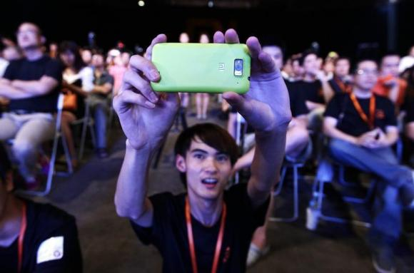 A user of Xiaomi uses his mobile phone to take a photo in Beijing