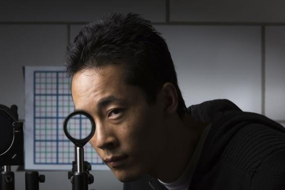 Handout photo of University of Rochester Ph.D. student Joseph Choi demonstrating a cloaking device using four lenses in Rochester