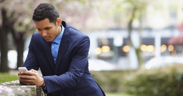 Man in suit using cell phone in urban park