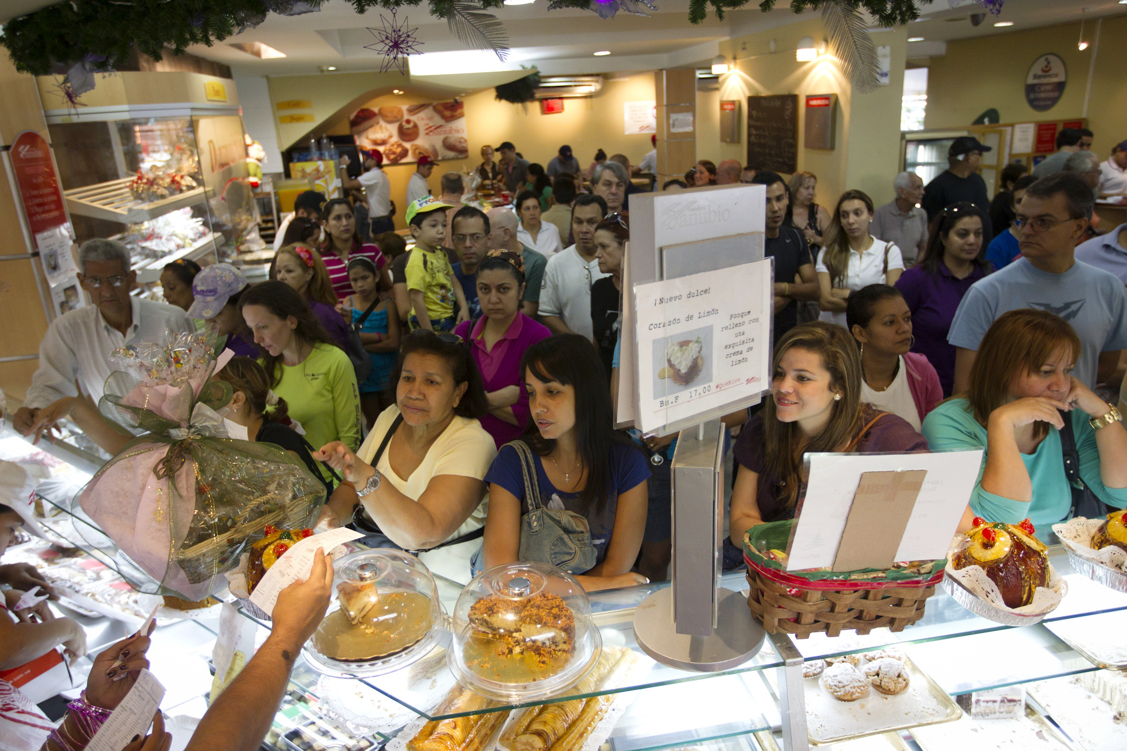 Customers wait their turn to buy ham bread at a pastry shop in Caracas