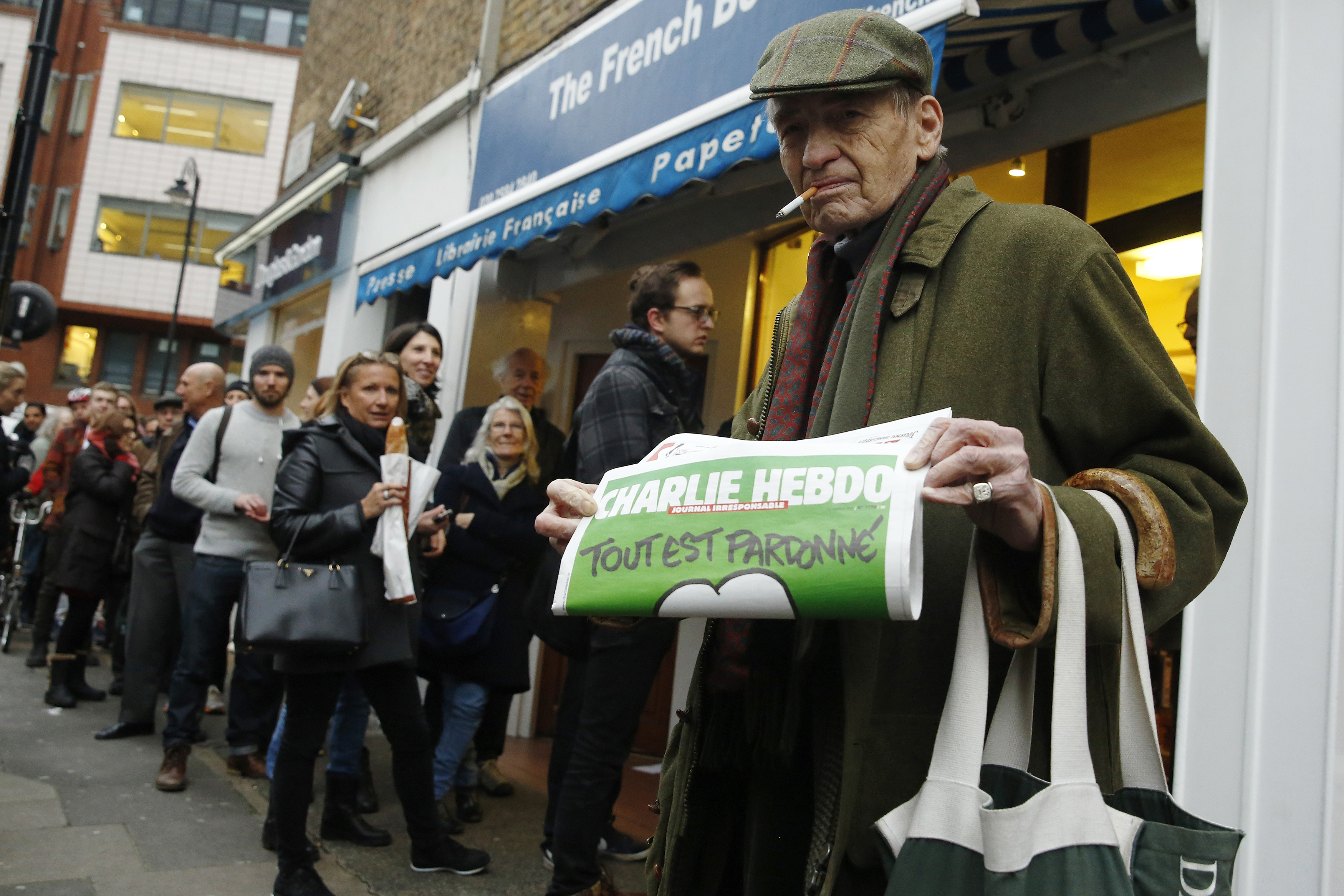A man poses with his copy of Charlie Hebdo whilst others queue, as it goes on sale in London