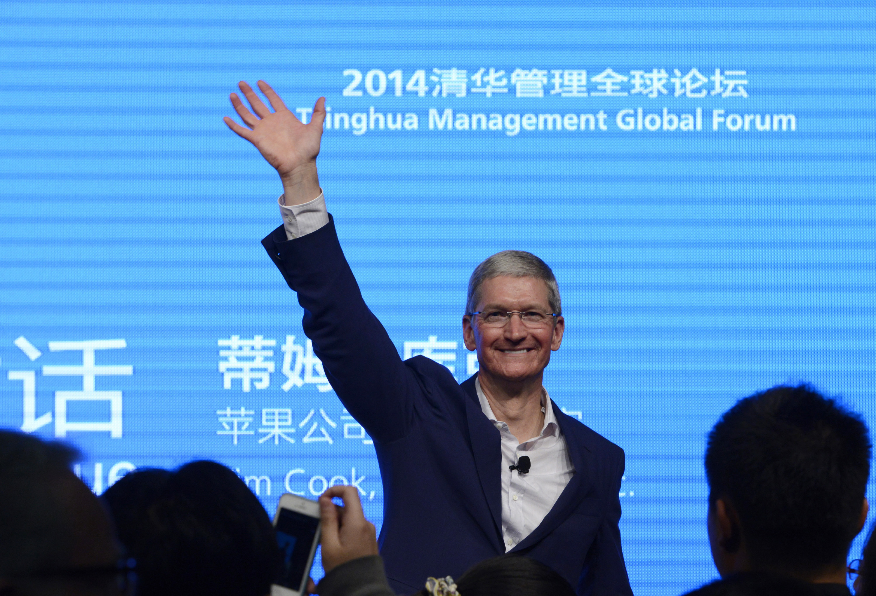 Apple CEO Tim Cook waves as he attends a talk at Tsinghua University in Beijing