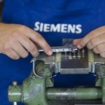 Siemens mechatronics apprentice works on bench vice during class at Siemens training centre in Berlin