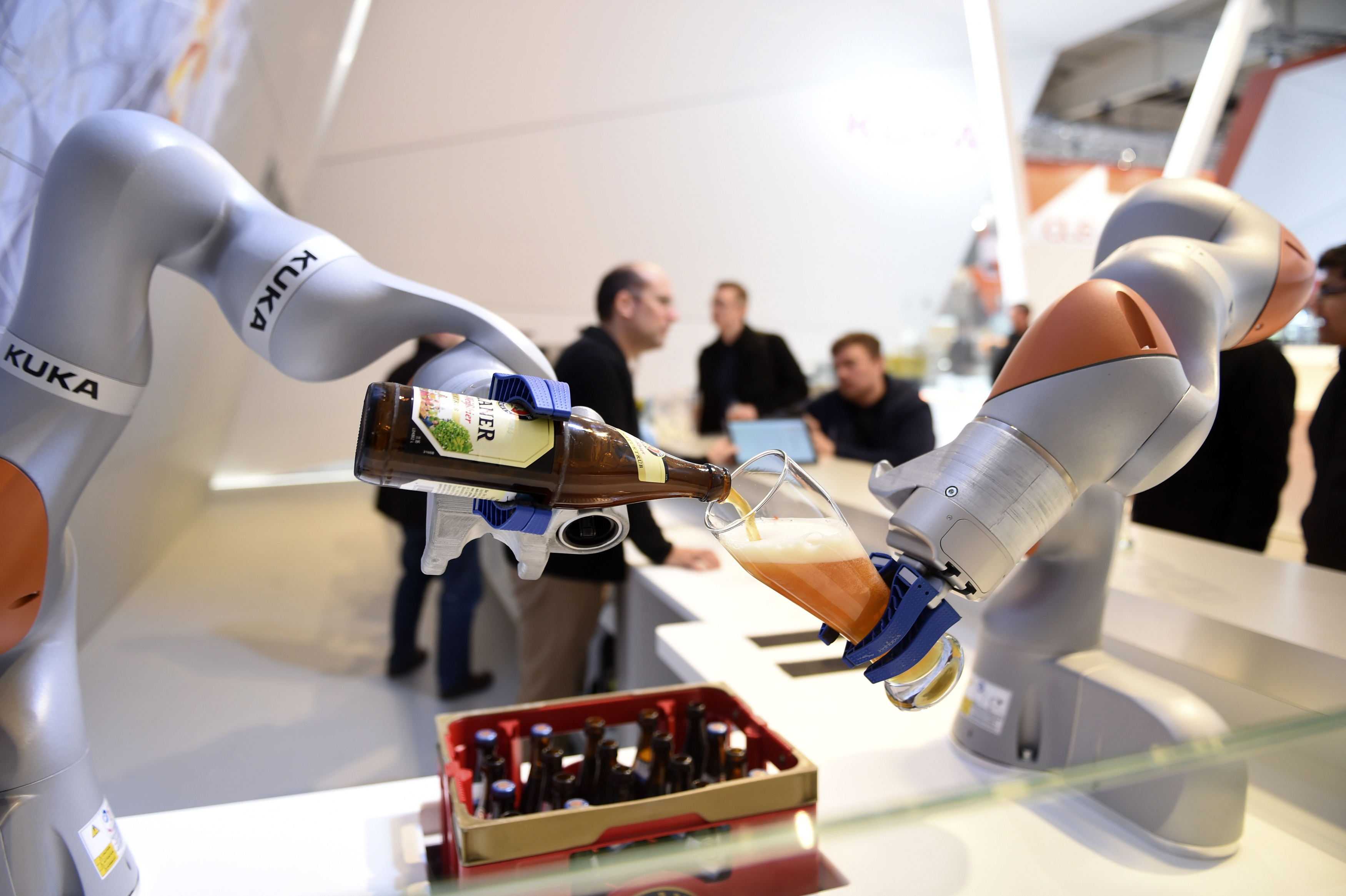Robots in the Kuka stand pour a beer into a glass at the Hannover Messe industrial trade fair in Hanover