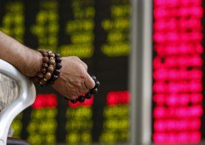 圖片來源:《達志影像》 圖片取自路透社 An investor holds onto prayer beads as he watches a board showing stock prices at a brokerage office in Beijing, China, July 6, 2015.     REUTERS/Kim Kyung-Hoon/File Photo - RTX2HPO2