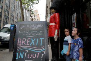 """達志影像不得重複使用!!! Children pose next to a chalkboard advertising a Brexit viewing event at """"The Churchill Tavern"""", a British theme bar, on the day where Britain votes whether or not to remain in the European Union in the Manhattan borough of New York, U.S., June 23, 2016. REUTERS/Andrew Kelly  - RTX2HUIX"""