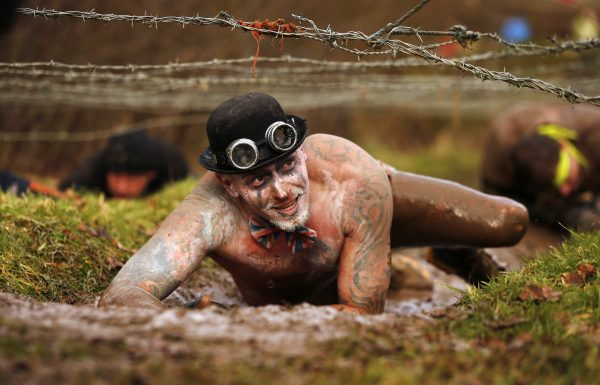 達志影像不得重複使用!!! A competitor crawls beneath barbed wire during the Tough Guy event in Perton, central England February 1, 2015. The annual event to raise cash for charity challenges thousands of international competitors in a cross country run followed by an assault course consisting of obstacles including water, fire and tunnels. REUTERS/Phil Noble (BRITAIN - Tags: SOCIETY SPORT TPX IMAGES OF THE DAY) - RTR4NSDW