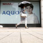 達志影像不得重複使用!!! A woman holding her umbrella walks past an advertisement poster for Sharp Corp's Aquos outside an electronics shop in Tokyo, Japan, July 31, 2015. Japan's Sharp Corp on Friday reported a bigger-than-expected quarterly operating loss and said it was exiting the TV business in the Americas in an attempt to shore up its finances after a bank-led bailout in May. REUTERS/Yuya Shino - RTX1MI13