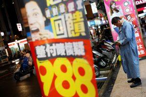 達志影像不得重複使用!!! A man looks at his mobile phone at a shopping district in Taipei, Taiwan May 27, 2016. REUTERS/Tyrone Siu - RTX2EHGY