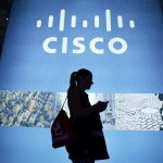 達志影像不得重複使用!!! A visitor walks past a Cisco advertising panel as she looks at her mobile phone at the Mobile World Congress in Barcelona February 27, 2014. REUTERS/Albert Gea (SPAIN - Tags: BUSINESS TELECOMS SCIENCE TECHNOLOGY) - RTR3FSCD