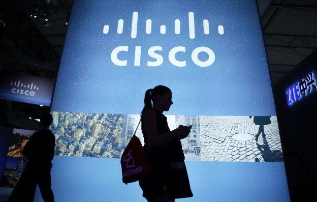 達志影像不得重複使用!!! A visitor walks past a Cisco advertising panel as she looks at her mobile phone at the Mobile World Congress in Barcelona February 27, 2014. REUTERS/Albert Gea (SPAIN - Tags: BUSINESS TELECOMS SCIENCE TECHNOLOGY) - RTR3FSCD