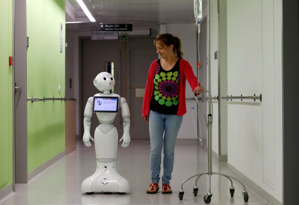 "達志影像不得重複使用!!! A woman walks with new recruit ""Pepper"" the robot, a humanoid robot designed to welcome and take care of visitors and patients, at AZ Damiaan hospital in Ostend, Belgium June 16, 2016. REUTERS/Francois Lenoir - RTX2GKO2"