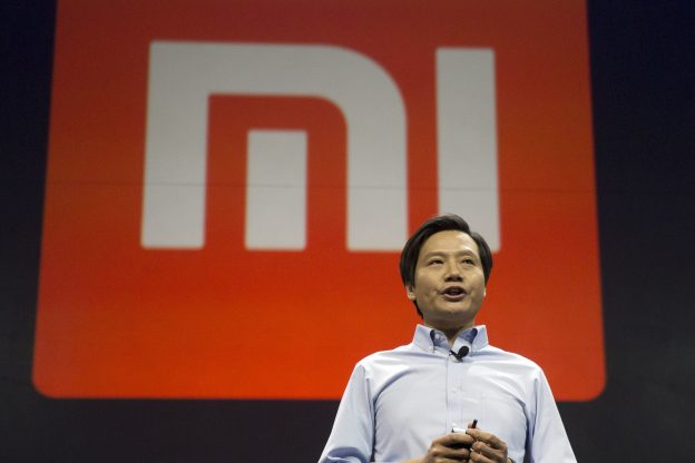 達志影像不得重複使用!!! Xiaomi Chairman Lei Jun stands in front of the logo of the Chinese smartphone maker, at a press event in Beijing, Thursday, Jan. 15, 2015. The Chinese manufacturer on Thursday unveiled a new model that Lei said has processor size and performance comparable to Apple's iPhone 6 but is thinner and lighter. (AP Photo/Ng Han Guan)