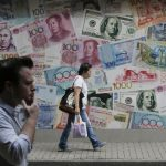 達志影像不得重複使用!!! People walk past a money exchange shop decorated with different currencies in Hong Kong, Monday, June 27, 2016. Japanese and Chinese stocks rose Monday but other Asian markets declined, crude prices fell further and U.S. shares appeared headed for a lower opening as jittery traders watched for more fallout from Britain's vote to exit the European Union. (AP Photo/Vincent Yu)