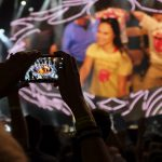 "達志影像不得重複使用!!! A fan uses her mobile phone to record a video of  The Rolling Stones as they perform during their final concert in the U.S. on their ""Zip Code"" tour in Orchard Park, New York July 11. 2015.  Photo taken July 11, 2015.  REUTERS/Hans Deryk - RTX1K4N8"