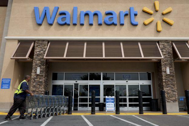 下載自美聯社 FILE - In this May 9, 2013, file photo, a worker pushes shopping carts in front of a Wal-Mart store in La Habra, Calif. Wal-Mart will now let you pay with your phone at all 4,600 stores nationwide. With Walmart Pay, the cashier scans a QR code on the phone screen to complete the payment. The effort is part of Wal-Mart's overall strategy to making shopping easier and faster. (AP Photo/Jae C. Hong, File)