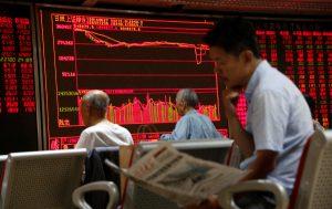 圖片來源:《達志影像》 圖片取自路透社 A man reads a newspaper in front of an electronic board at a brokerage house in Beijing, China, June 27, 2016.   REUTERS/Kim Kyung-Hoon - RTX2IDLO