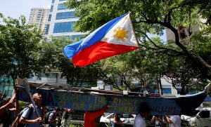 下載自路透 A Philippine national flag flutters on a part of a fishing boat with anti-China protest signs, as demonstrators march towards the Chinese Consulate, over the South China Sea disputes, in Makati City, Metro Manila, Philippines July 12, 2016. REUTERS/Erik De Castro - RTSHHBY