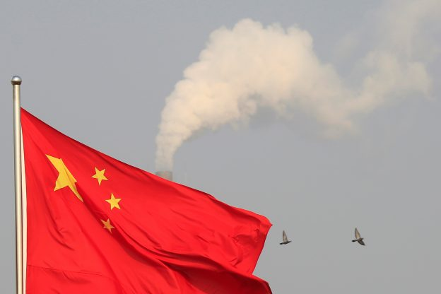 圖片來源:《達志影像》 圖片取自路透社 Birds fly past the chimney of a thermal power plant as China's national flag flutters in a suburb in Shanghai January 9, 2015. REUTERS/Aly Song/File Photo - RTX2HAX1