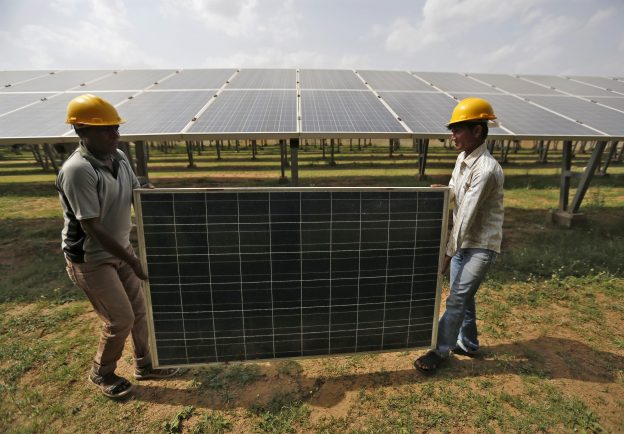 下載自路透 Workers carry a damaged photovoltaic panel inside a solar power plant in Gujarat, India, July 2, 2015. India's $100 billion push into solar energy over the next decade will be driven by foreign players as uncompetitive local manufacturers fall by the wayside, no longer protected by government restrictions on the sector. REUTERS/Amit Dave - RTX1IR4N