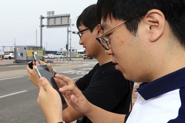 下載自美聯社 HOLD FOR USE WITH STORY SLUGGED SOUTH KOREA POKEMON GO BY YOUKYUNG LEE, In this July 13, 2016 photo, Two South Koreans play the Pokemon Go game with mobile phones in Sokcho, South Korea. The seaside South Korean city of Sokcho is enjoying a surge of visitors who are wandering the streets at all hours as they look at their smartphones. Why? It appears to be the only place in the country where Pokemon Go players can chase the mobile game's virtual monsters.(Lee Jong-hun/Yonhap via AP) KOREA OUT