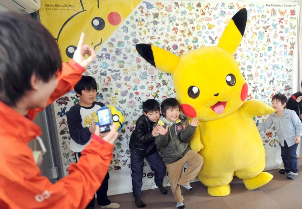 """下載自美聯社 Evacuee children pose with Pikachu during """" Pokemon with You Wagon,''  activity at a temporary housing unit of Matsuiwa Middle School, in Kesennuma, Miyagi Prefecture on March 10, 2013, ahead of the second anniversary of the Great East Japan Earthquake and  the ensuing tsunami on March 11, 2011. About 20 kids and parents took part in the event  and they were encouraged by the character. The wagon has visited more than 100  the make-shift housings since Feburaary last year.  ( The Yomiuri Shimbun via AP Images )"""