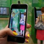 "下載自路透 A woman plays the augmented reality mobile game ""Pokemon Go"" by Nintendo, as a visitor uses an automated teller machine (ATM) at a branch of Sberbank in central Krasnoyarsk, Siberia, Russia, July 20, 2016. REUTERS/Ilya Naymushin - RTSIVYJ"