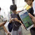 "下載自美聯社 People gaze at their smartphones as they play ""Pokemon Go"" at Akihabara district in Tokyo, Friday, July 22, 2016.   The wait is over for ""Pokemon Go"" fans in Japan. Users began tweeting it was available Friday morning, and the Pokemon Co. and the developer of the augmented reality game, U.S.-based Niantic Inc., confirmed its launch shortly after. (AP Photo/Eugene Hoshiko)"