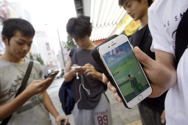 """下載自美聯社 People gaze at their smartphones as they play """"Pokemon Go"""" at Akihabara district in Tokyo, Friday, July 22, 2016.   The wait is over for """"Pokemon Go"""" fans in Japan. Users began tweeting it was available Friday morning, and the Pokemon Co. and the developer of the augmented reality game, U.S.-based Niantic Inc., confirmed its launch shortly after. (AP Photo/Eugene Hoshiko)"""