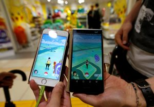"""下載自路透 Men pose with their mobile phone displaying the augmented reality mobile game """"Pokemon Go"""" by Nintendoa in front of a shop selling Pokemon goods in Tokyo, Japan July 22, 2016. REUTERS/Toru Hanai - RTSJ4L2"""