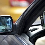 下載自路透 A taxi driver is reflected in a side mirror as he uses the Didi Chuxing car-hailing application in Beijing, China, September 22, 2015. REUTERS/Jason Lee/File Photo - RTX2E3TE