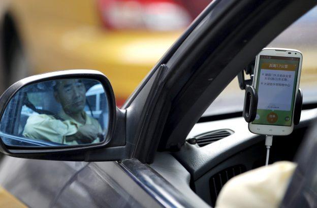 下載自路透 A taxi driver is reflected in a side mirror as he uses the Didi Chuxing car-hailing application in Beijing, China, September 22, 2015. REUTERS/Jason Lee/File Photo - RTX2E3TE