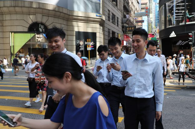 "下載自美聯社 Fans maneuver their smartphones as they play ""Pokemon Go"" in Hong Kong, Monday, July 25, 2016. Pokemon fans used the app on Monday as it was released to both iPhone and Android users. (AP Photo/Kin Cheung)"
