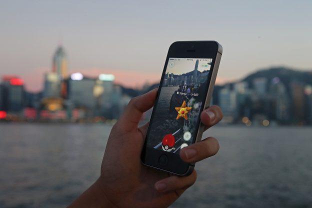 """下載自美聯社 A fan maneuvers his smartphone as he plays """"Pokemon Go"""" in Hong Kong, Monday, July 25, 2016. Pokemon fans used the app on Monday as it was released to both iPhone and Android users. (AP Photo/Kin Cheung)"""
