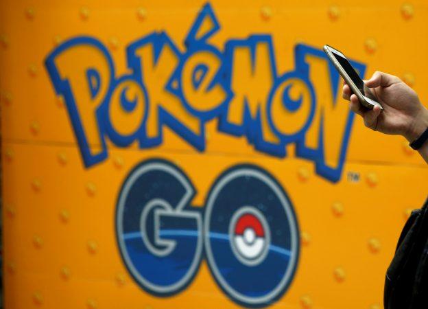 下載自路透 A man uses a mobile phone in front of an advertisement board bearing the image of Pokemon Go at an electronic shop in Tokyo, Japan, July 27, 2016.   REUTERS/Kim Kyung-Hoon - RTSJUQ0