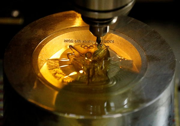 下載自路透 A machine works on a Rio 2016 Olympic medal at the Casa da Moeda do Brasil (Brazilian Mint) in Rio de Janeiro, Brazil, June 28, 2016. REUTERS/Sergio Moraes - RTX2IRUY