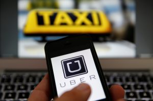 An illustration picture shows the logo of car-sharing service app Uber on a smartphone next to the picture of an official German taxi sign September 15, 2014.    REUTERS/Kai Pfaffenbach/Illustration/File Photo - RTX2GON9