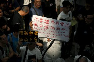 下載自路透 A protester carries a banner, as hundreds of airlines related staff and citizens protest against Hong Kong Chief Executive Leung Chun-ying, who allegedly put pressure on airport staff to help his daughter retrieve a bag left outside of restricted areas, during a demonstration at the arrival hall of the Hong Kong Airport in Hong Kong, China April 17, 2016. REUTERS/Bobby Yip - RTX2AAKK