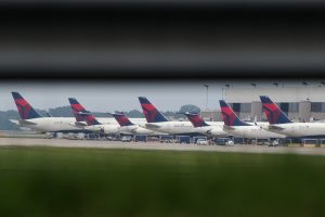 Delta planes are parked at gates at Atlanta's Hartsfield International Airport in Atlanta, Monday, Aug. 8, 2016, as Delta Air Lines grounded all flights after after a power outage hit its computer systems globally. (AP Photo/Branden Camp)