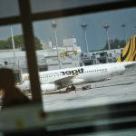A passenger walks past a reflection of a Tiger Airways plane sitting on the tarmac at Changi Airport in Singapore July 21, 2014. Singapore's Tiger Airways Holdings Ltd reported a wider loss in the quarter ended June, hurt by one-time costs related to the shutting down of its Indonesian venture. Picture taken July 21, 2014.  REUTERS/Edgar Su (SINGAPORE - Tags: TRANSPORT BUSINESS) - RTR3ZSVF