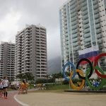 下載自美聯社 Athletes walk past the Olympic Rings at the Olympic Village Barra during the media day prior to the Rio 2016 Olympic Games in Rio de Janeiro, Brazil, 2 August 2016. The Rio 2016 Olympic Games take place from 05 to 21 August. Russian flags are attached to the building. Photo by: Michael Kappeler/picture-alliance/dpa/AP Images