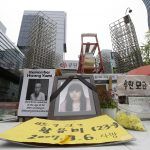 "下載自美聯社 In this April 22, 2016 photo, portraits of former Samsung semiconductor factory worker Hwang Yu-mi who died from leukemia in 2007, are displayed outside Samsung buildings in Seoul, South Korea. An Associated Press investigation has found South Korean authorities have, at Samsung's request, repeatedly withheld from workers and their bereaved families crucial information about chemicals they were exposed to at its computer chip and liquid crystal display factories. Sick workers are supposed to have access to such data through the government or the courts so they can apply for workers' compensation from the state. Without it, government officials commonly reject their cases. The yellow banner in the foreground, reads: ""Hwang Yu-mi, 23, died on March 6 in 2007."" (AP Photo/Ahn Young-joon)"