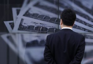 圖片來源:《達志影像》 圖片取自路透社 A businessman looks at a screen displaying a photo of  U.S. 100 dollar bank notes in Tokyo April 8, 2013. The yen hit fresh lows against a host of major currencies on Monday, resuming its slide after the Bank of Japan lost no time in launching its new easing policy to underline its determination to beat deflation.   REUTERS/Toru Hanai (JAPAN - Tags: BUSINESS) - RTXYCYV