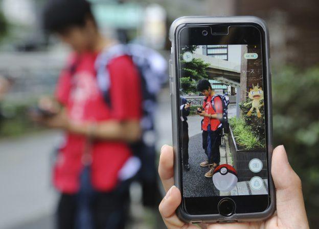 """圖片來源:《達志影像》 圖片取自美聯社 FILE - In this July 22, 2016 file photo, Japanese students play """"Pokemon Go"""" in the street as its released in Tokyo. Japanese video game maker Nintendo Co. has sunk into a loss of 24.53 billion yen ($232 million) for the fiscal first quarter through June, 2016 despite the global success of the """"Pokemon Go"""" augmented reality game. The result Wednesday, July 27, 2016, was worse than the 673 million yen ($6.4 million) profit forecast by analysts surveyed by FactSet. (AP Photo/Koji Sasahara, File)"""