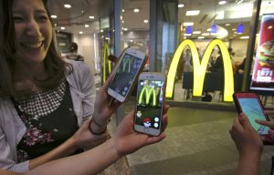"Women play ""Pokemon Go"" in front of a McDonald's restaurant in Tokyo, Friday, July 22, 2016.  The Japan launch of ""Pokemon Go"" on Friday included the game's first partnership with an outside company: fast-food giant McDonald's. About 400 McDonald's Japan outlets are ""gyms,"" where players can battle on their smartphones. The other 2,500 are ""Pokestops,"" where they can get items to play the game. The hope is, presumably, that they may also buy a Big Mac in the process.(AP Photo/Koji Sasahara)"