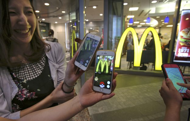 """Women play """"Pokemon Go"""" in front of a McDonald's restaurant in Tokyo, Friday, July 22, 2016.  The Japan launch of """"Pokemon Go"""" on Friday included the game's first partnership with an outside company: fast-food giant McDonald's. About 400 McDonald's Japan outlets are """"gyms,"""" where players can battle on their smartphones. The other 2,500 are """"Pokestops,"""" where they can get items to play the game. The hope is, presumably, that they may also buy a Big Mac in the process.(AP Photo/Koji Sasahara)"""