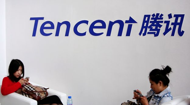 下載自路透 Visitors use their smartphones underneath the logo of Tencent at the Global Mobile Internet Conference in Beijing May 6, 2014. REUTERS/Kim Kyung-Hoon/File Photo - RTX2JXLA