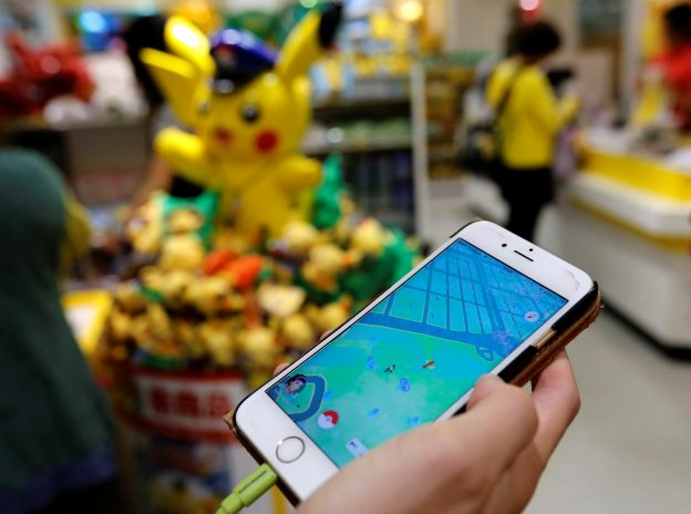 "A man plays the augmented reality mobile game ""Pokemon Go"" by Nintendo in front of a shop selling Pokemon goods in Tokyo, Japan July 22, 2016. REUTERS/Toru Hanai - RTSJ4L3"