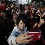 下載自路透 Supporters of South Korea's presidential candidate Park Geun-hye of ruling Saenuri Party hold up smart phones to take pictures during her election campaign rally in Seoul, December 15, 2012. Former human rights lawyer and presidential candidate of the main opposition Democratic United Party Moon Jae-in, challenger to conservative and right winger Park Geun-hye, was 1.5-3.5 percentage points behind, compared with a gap of up to 7.5 points a week ago. South Korea bans the publication of opinion polls from Thursday. Moon's gains came after independent candidate Ahn Cheol-soo dropped out of the running and threw his support behind Moon's bid to beat Park, the daughter of South Korea's former military dictator Park Chung-hee, in the December 19 vote.   REUTERS/Kim Hong-Ji (SOUTH KOREA - Tags: POLITICS ELECTIONS) - RTR3BL9B