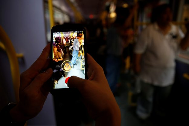 "下載自路透 A passenger plays the augmented reality mobile game ""Pokemon Go"" by Nintendo inside a bus in Hong Kong, China August 12, 2016. REUTERS/Tyrone Siu - RTX2LZ54"